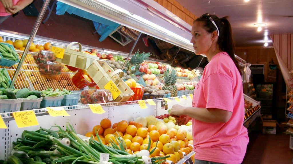 A grocer stands in front of her fresh produce cooler.