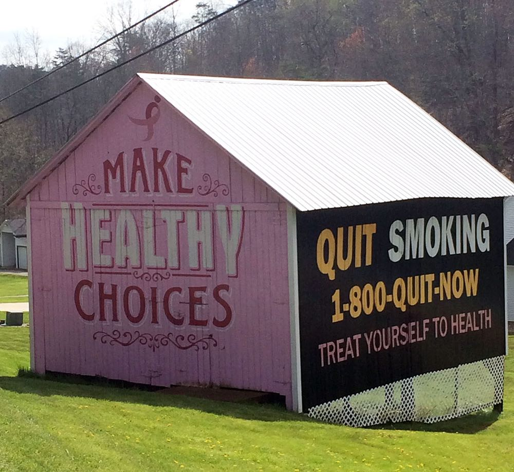 A barn painted with colorful health slogans.